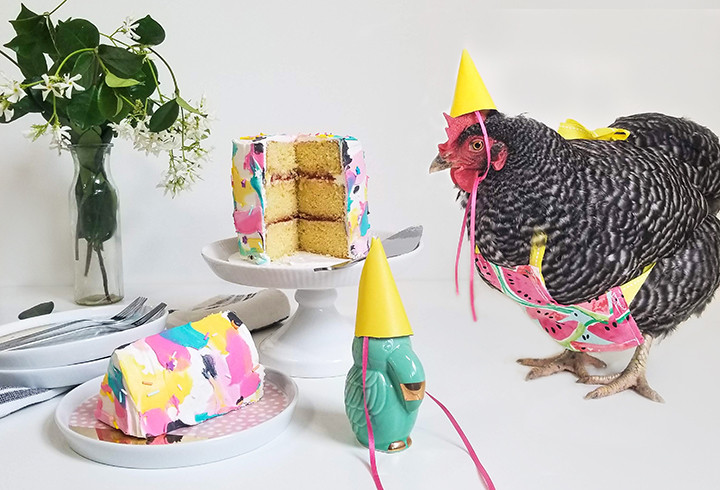 chicken wearing a party hat with cake