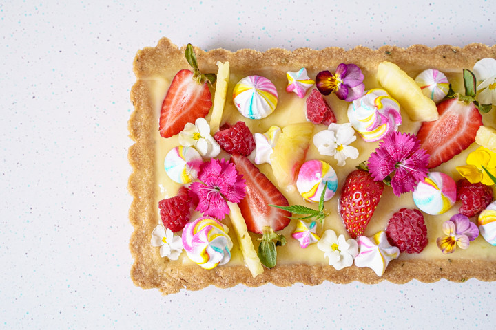 pineapple meringue tart with fruit and edible flowers