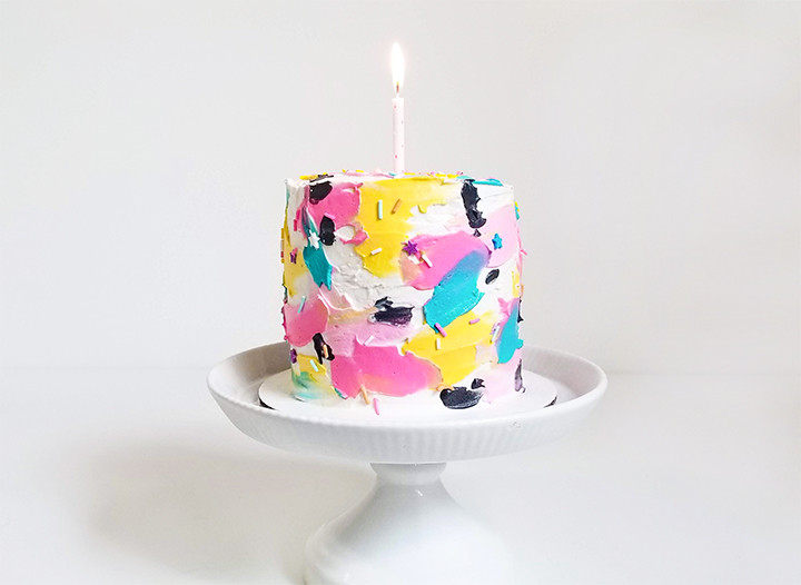 painted buttercream cake with a candle