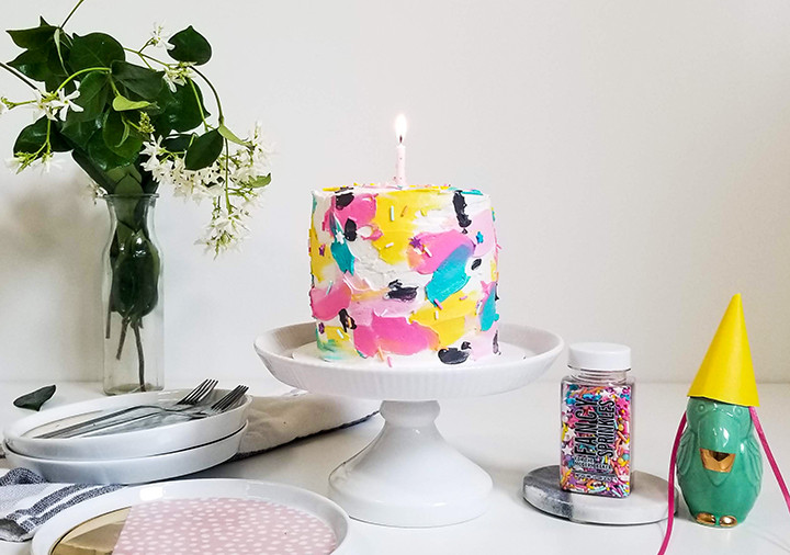 painted buttercream cake on a cake stand