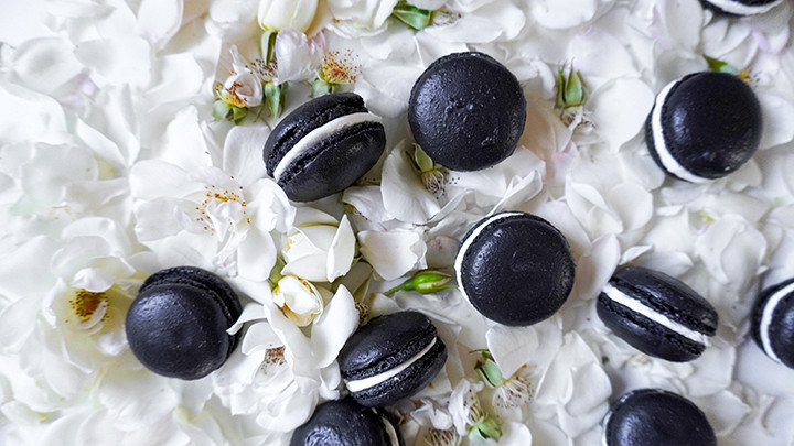 black macaron cookies on white roses