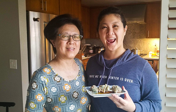 mom and daughter holding plate of dumplings