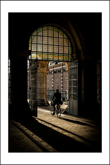 Man biking under The Rijksmuseum Amsterdam