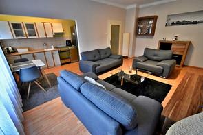 Obývací pokoj s pohledem do chodby a kuchyně.
