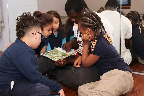 Omar with kids reading.jpeg