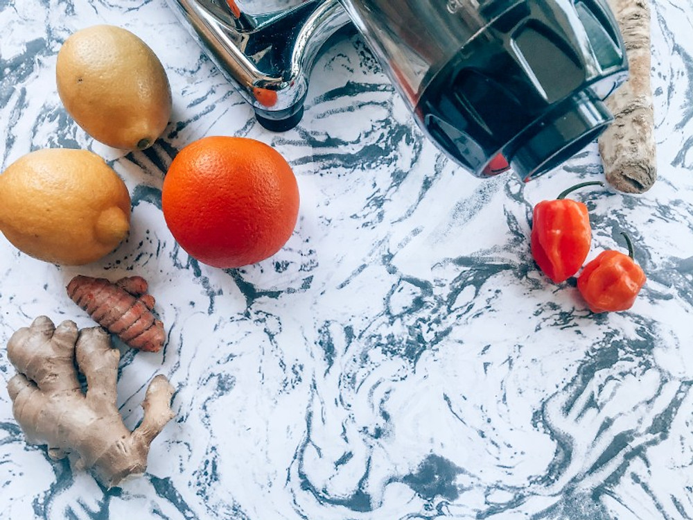 Cold press juicer with lemons, orange, ginger, turmeric, horseradish and habanero peppers.