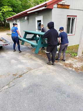 Lions Camp Pride volunteers rearranging outdoor furniture