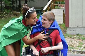 Happy camper in wheelchair with camp counselor