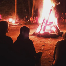 Lions Camp Pride campers around bonfire at night