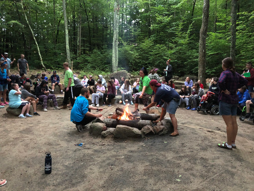 Campers roasting marshmallows at fire pit