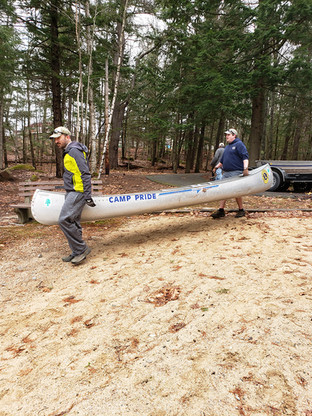 Adults bringing Lions Camp Pride canoes to the lake