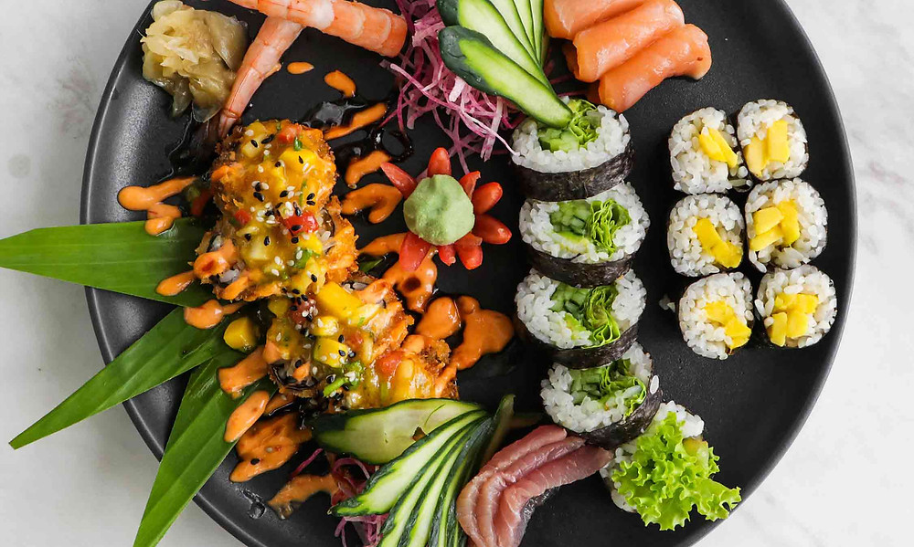 black circular plate with different types of sushi to illustrate international sushi day