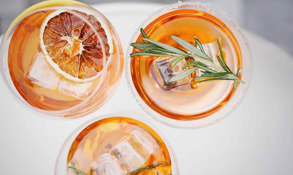 three orange cocktails with ice