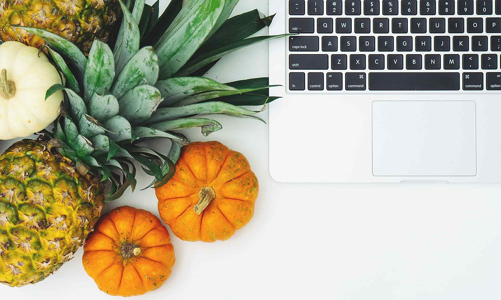 fruit and vegetables next to a computer