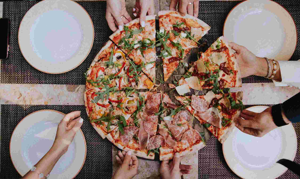 people sharing pizza with plates on table