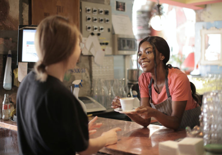 bakery where a woman gives a drink to another person over a counter