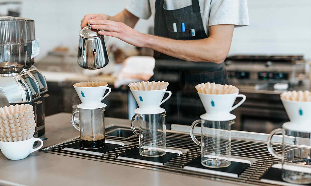 barista pouring coffee into mugs in coffee shop
