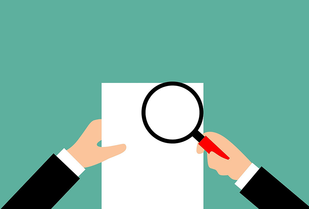 person with magnifying glass over piece of paper to demonstrate food safety due diligence meaning