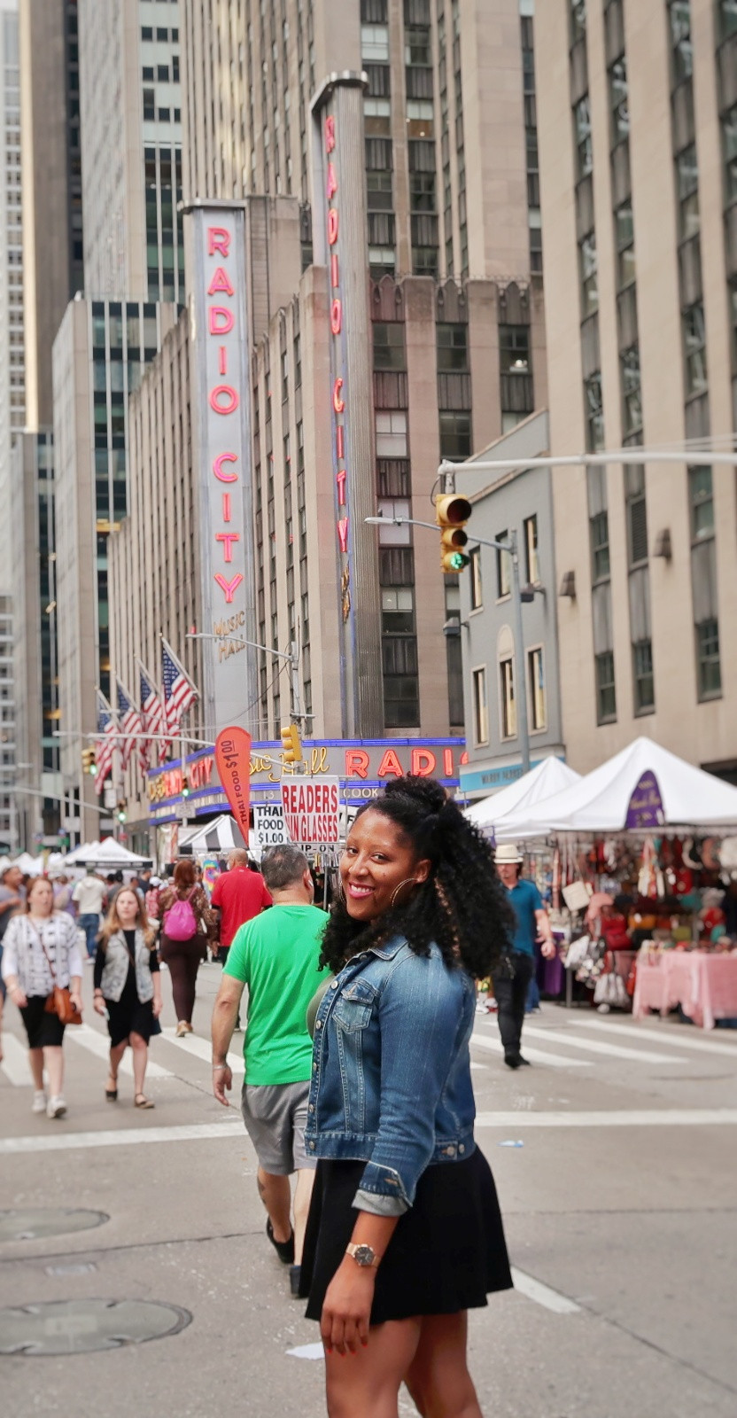 Woman standing in the middle of street in front of Radio City Music Hall