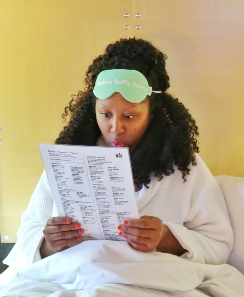 Woman sitting in a bed while holding a hotel menu