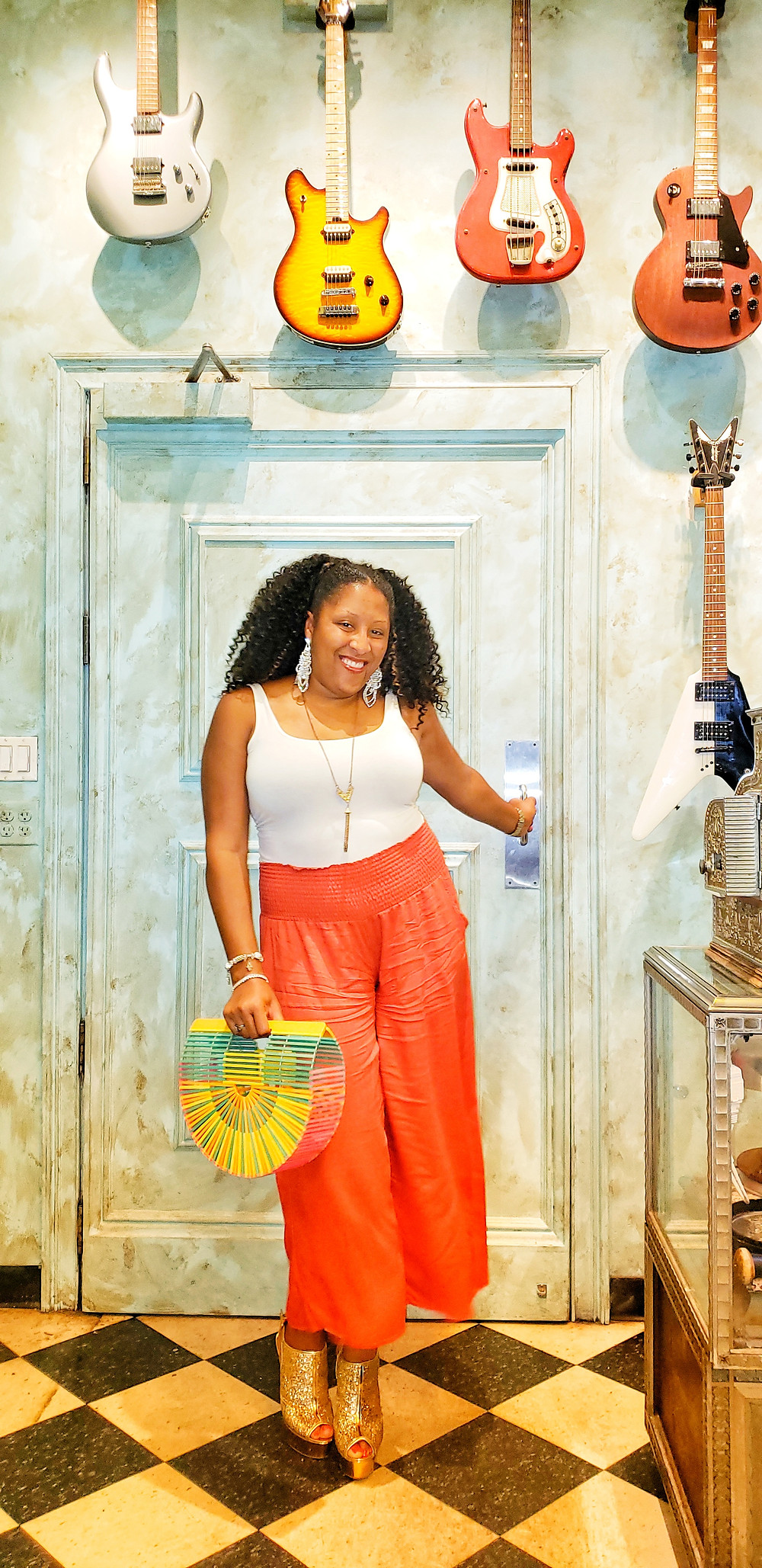 Woman standing in front of a blue door with guitars above
