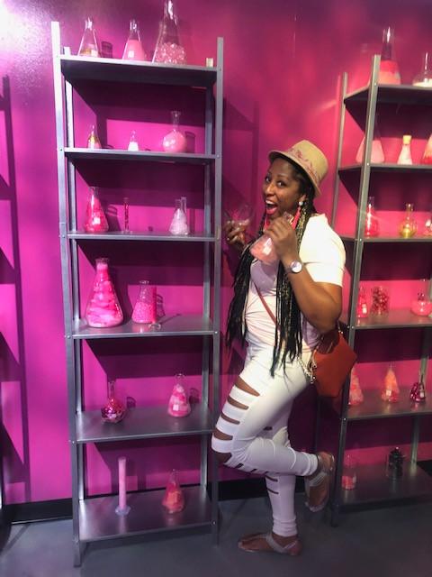 Woman beside a shelf full of chemistry beakers