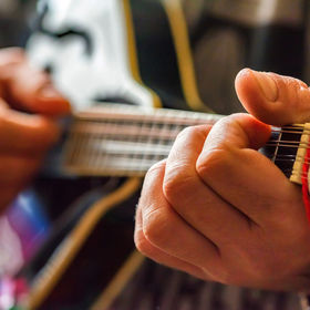 Close up hands of man playing 8-string m