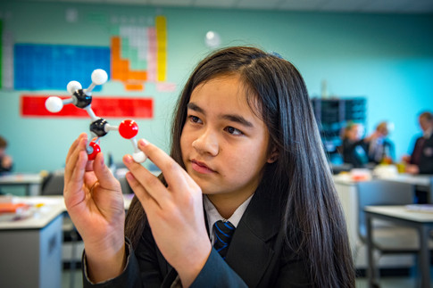 girl in science class with molecule model