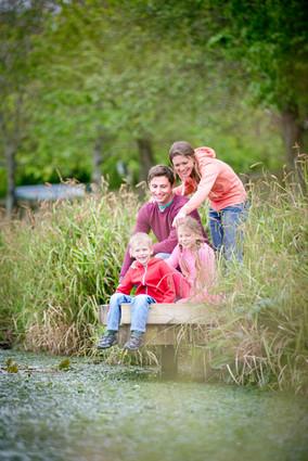 family photographed next to fishing lake