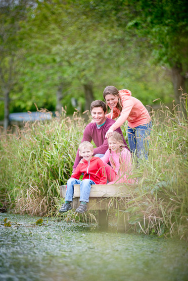 family photographed next to fishing lake