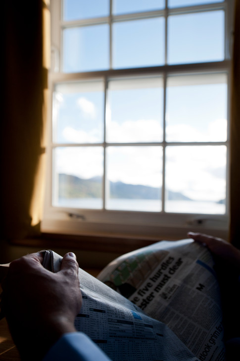 man reading newspaper with view outside window