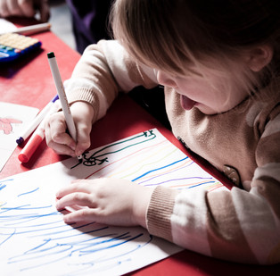 young girl photographed drawing at scho