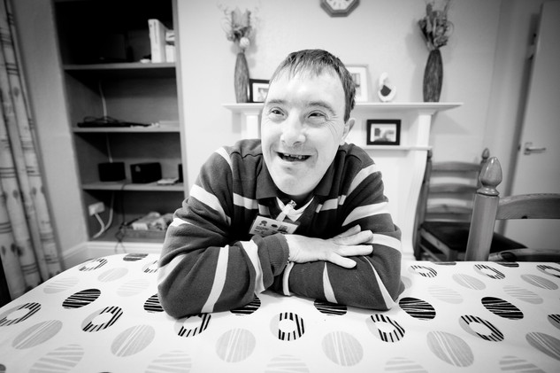 downs syndrome man at dining table