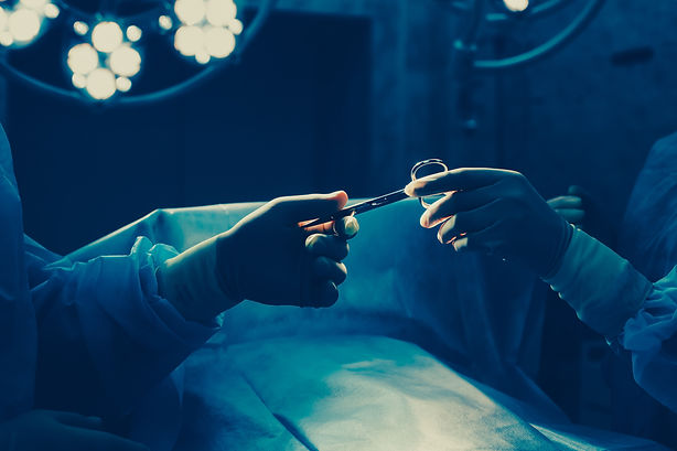 Close-up of gloved hands holding surgical scissors.jpg