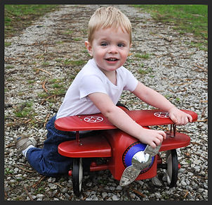 child playing with red airplane toy outside