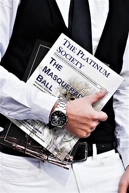 Elegant man holding a copy of The Platinum Society Magazine