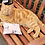 Ginger cat lying on a wooden garden bench with a honeysuckle cuddle cushion