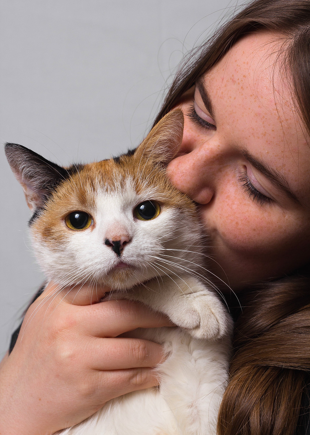 Woman Hugging a Ginger and White Cat