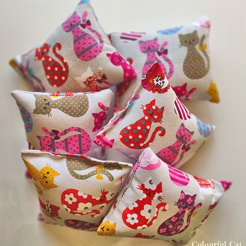 Bundle of six honeysuckle cuddle cushions decorated with a pink cat print placed on a white background