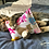 Tabby cat lying on a bed chewing and cuddling a honeysuckle cuddle cushion