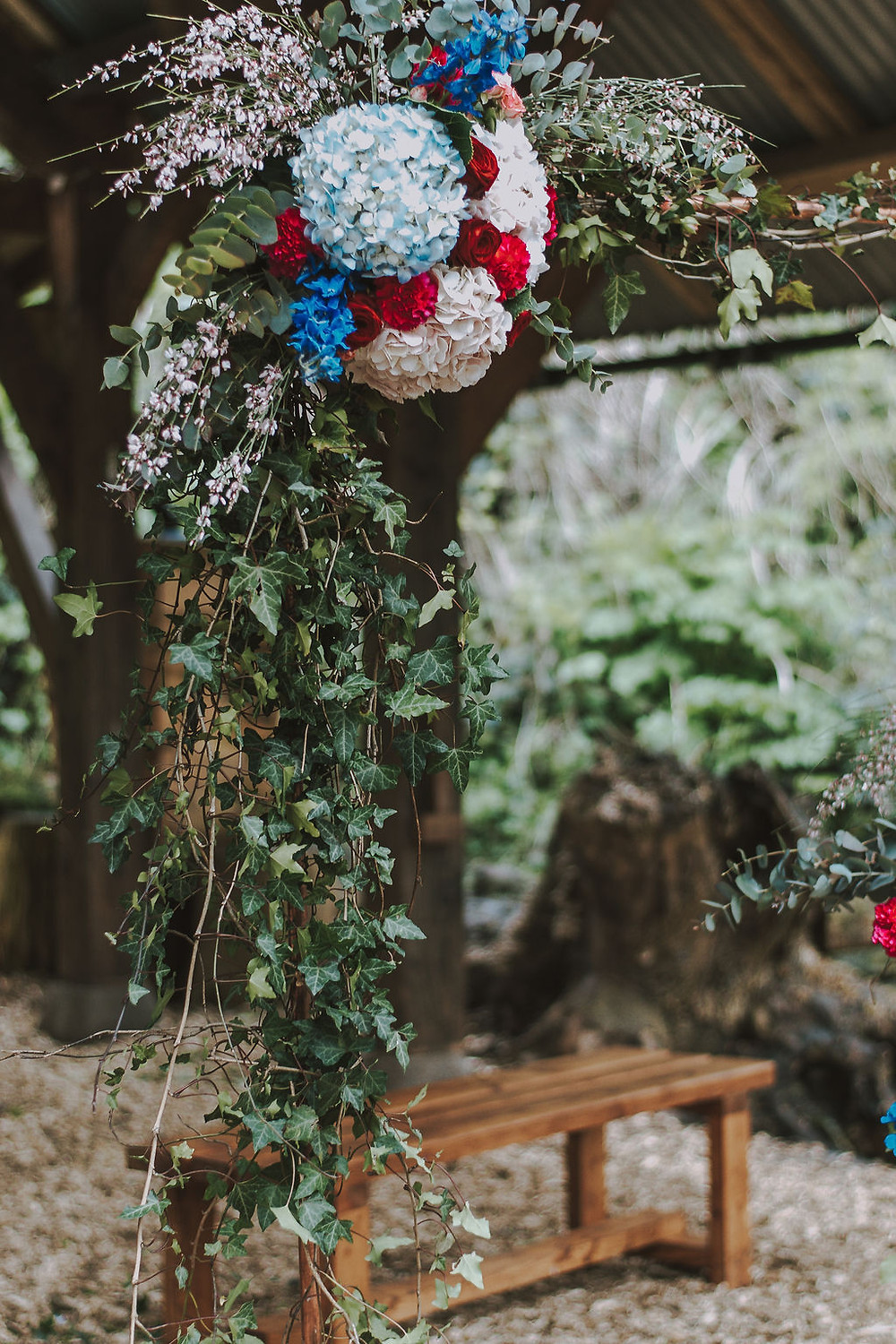 Outdoor red blue pink floral arch installation wedding inspiration