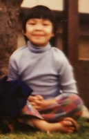 An Asian American girl seated cross legged and smiling
