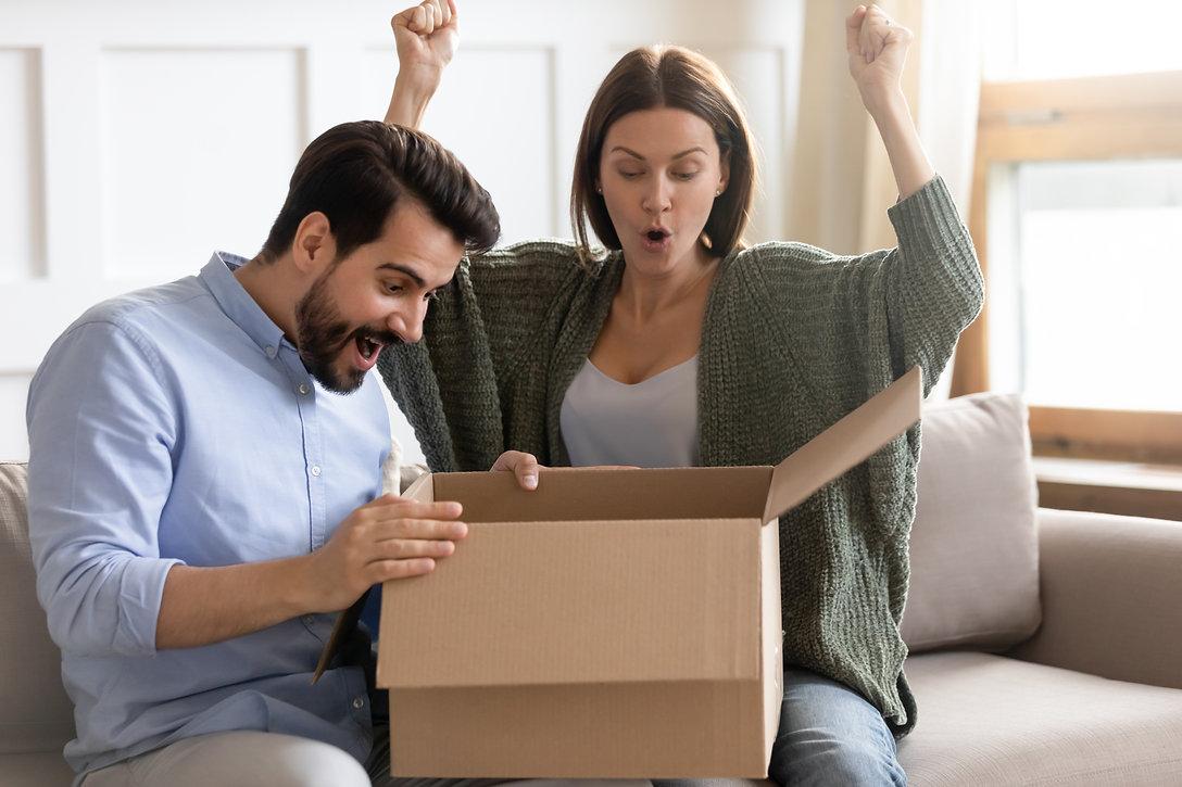 Overjoyed married couple opening carton