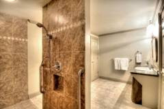 This is a walk-in bathroom with a roll-in shower. The entire bath has a marble floor.