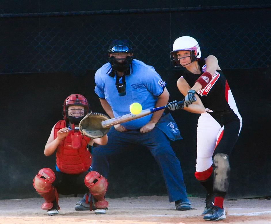 Softball player hitting the ball