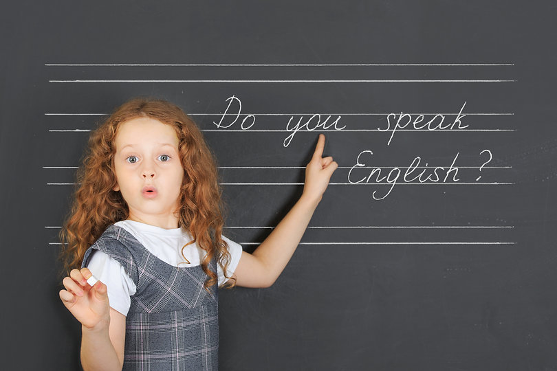 Surprised redhead girl asks a question -  Do you speak English, stand near blackboard in the classro