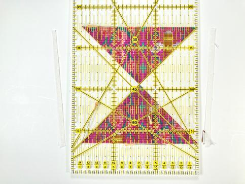 Răsuciți clepsidra 90 de grade. Aliniați intersecția liniilor de 7 cm verticală și 45 de grade de pe riglă cu mijlocul clepsidrei. Laturile tăiate anterior, acum în poziție orizontală, trebuie să fie aliniate cu liniile orizontale pe riglă. Astfel ne asigurăm că vom avea un pătrat perfect, și nu un paralelogram strâmb. În acest moment, linia pe care o vom tăia din partea dreaptă ar trebui să se alinieze perfect cu colțurile triunghiurilor materialelor imprimate. Tăiați latura din dreapta. Repetați pașii pentru a tăia ultima latură.