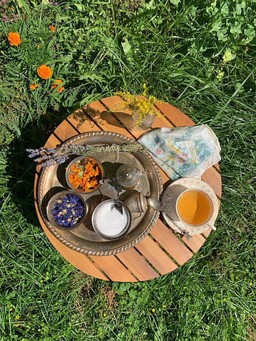 A top down view of a small round wooden slatted table sitting in the grass. An antique metal tray holds a tea steeper, a tea pot, bowls of blue and orange flowers, a sugar bowl, and a bundle of lavender. A porcelain tea cup and saucer are next to the tray and there is a glass bottle of flowers and a floral handkerchief on the table as well.