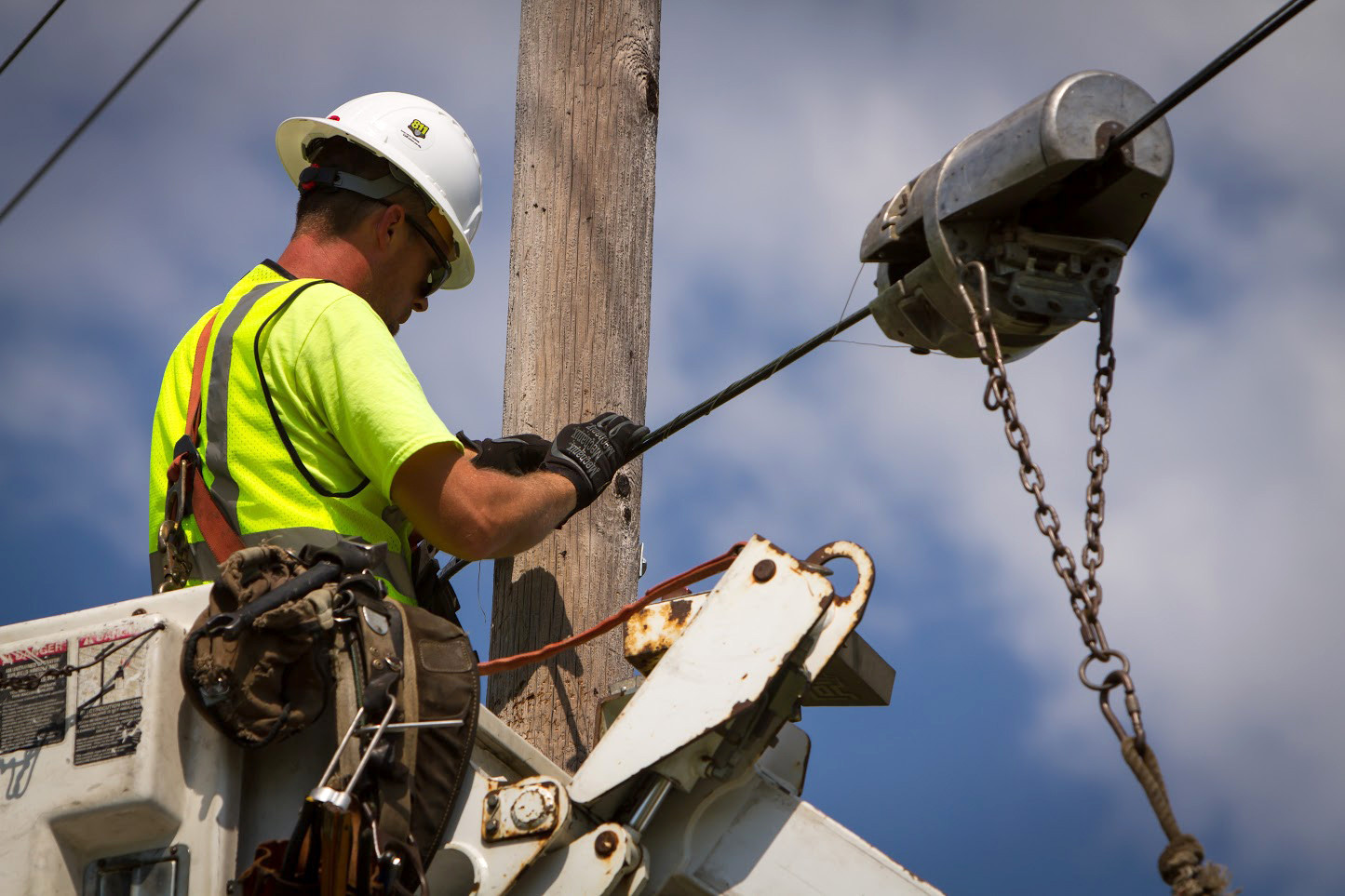 Man on telephone pole installing areial cabling