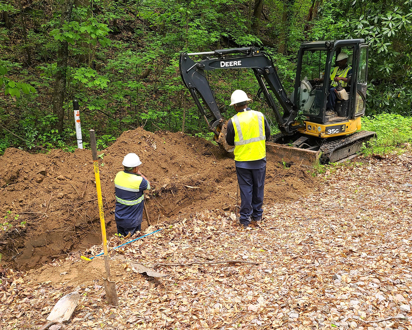 Men supervise mini excavator digging trench for underground cable construction